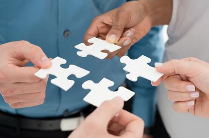 mehrere Personen setzen Puzzleteile zusammen